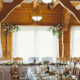 Drewno i kwiaty – dekoracja stołu prezydialnego – Karczma na Lednicy