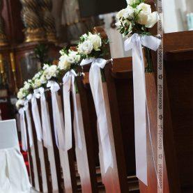Bukiety białych kwiatów na ławkach – wystrój kościoła w Owińskach