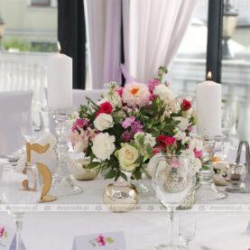 Niska kompozycja na paterce, eleganckie świece oraz złote dodatki – wystrój sali w Dworku Róża Poraja
