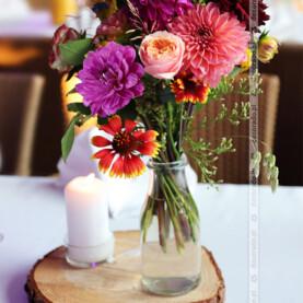 Bukiety naturalnych kwiatów w butelkach na plastrach drewna – dekoracja ślubna w Restauracji Oaza