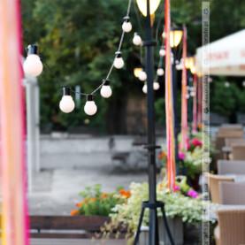 Łańcuchy żarówek i kolorowe wstążki – dekoracja tarasu – Restauracja Oaza