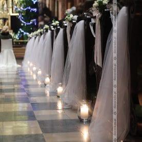 Elegancka dekoracja ławek – kwiaty, tiul, lampiony – Katedra Poznańska