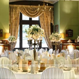 Kompozycje kwiatowe na wysokich świecznikach – dekoracja stołów weselnych w Pałacu w Wąsowie